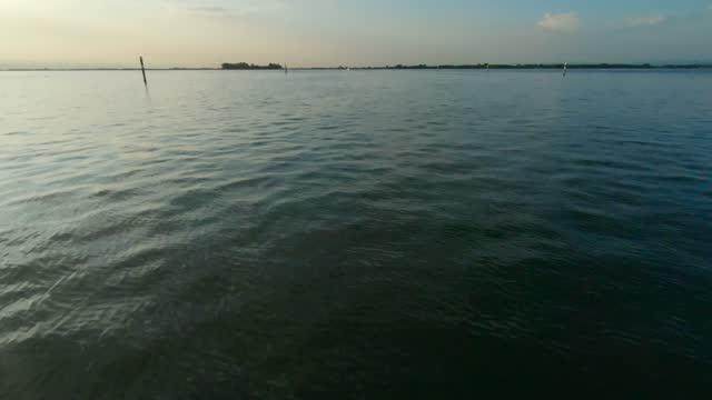 vídeos de stock, filmes e b-roll de boat cruising in the grado lagoon, italy - superfície de água