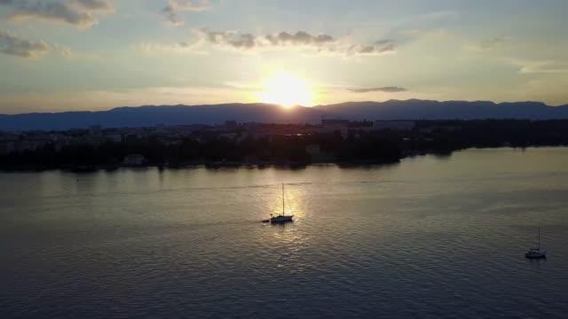 Boat cruising on pristine Lake Geneva, Switzerland at sunset