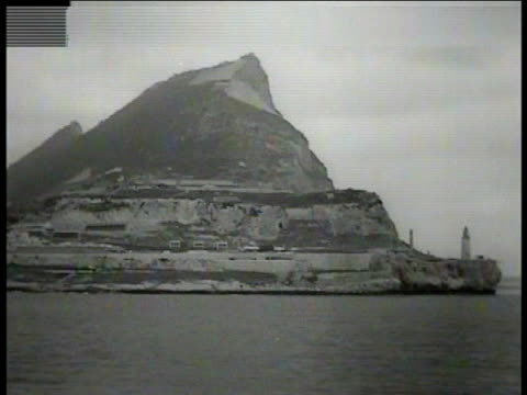 stockvideo's en b-roll-footage met rock of gibraltar from west, europa point lighthouse at tip . british reinforcement soldiers crowded on ship's deck. - west europa