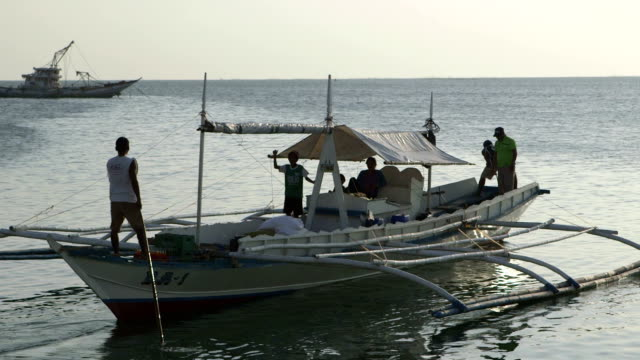 a boat disembarks from dock onto the ocean - philippines stock videos & royalty-free footage