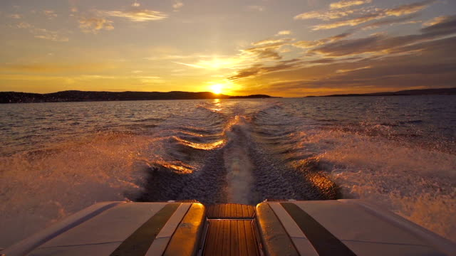 boat driving away from sunset - nautical vessel stock videos & royalty-free footage