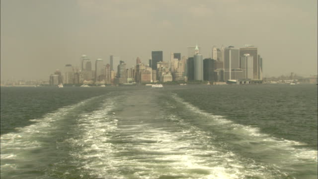 vídeos de stock, filmes e b-roll de a boat engine leaves a wake in the hudson river near the new york city skyline. available in hd. - porto de nova york