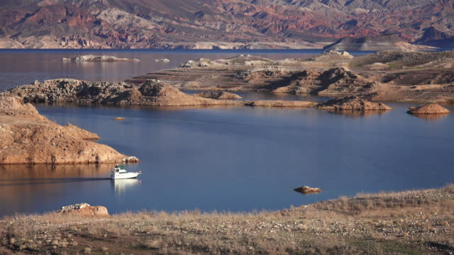 a boat enters a narrow channel on lake mead - lake mead video stock e b–roll