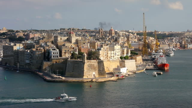 stockvideo's en b-roll-footage met a boat enters the grand harbour - valletta