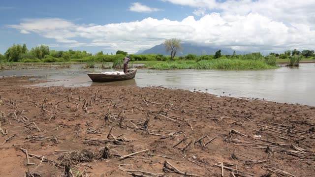 a boat ferrying food supplies across flooded farmland near phalombe, with maize crops destroyed by the floods in the foreground. - extreme weather stock videos & royalty-free footage