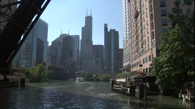 A boat floats down the Chicago River toward the Chicago skyline.