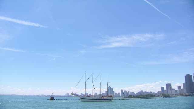boat floats on lake michigan with chicago skyline in background near navy pier on july 4 2014 in chicago illinois - lake michigan stock videos & royalty-free footage