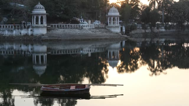 Boat floats on pond in public garden at sunrise