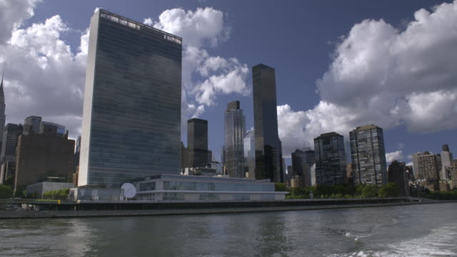 boat glides on the east river near the un. - vereinte nationen stock-videos und b-roll-filmmaterial