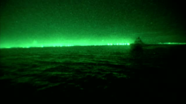 a boat glides over the ocean at night. - night vision stock videos and b-roll footage
