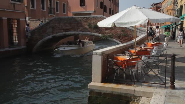 ws ld boat going under bridge in canal / venice, italy - motoscafo da competizione video stock e b–roll