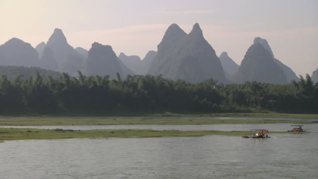 ws boat going up li river with karst scenery beyond / yangshuo, guangxi, china - li river stock videos & royalty-free footage