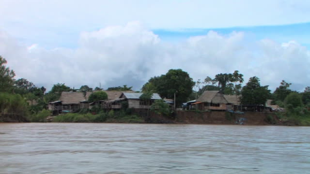 WS TS boat POV houses on riverbank from river/ Manu National Park, Peru