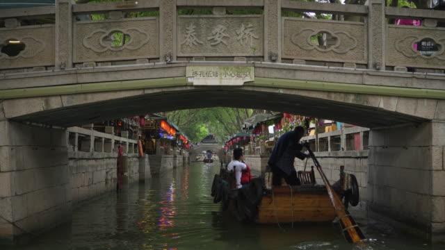 ws boat in canal moving under bridge, tongli, wujiang district, suzhou, jiangsu province, china - china east asia stock videos & royalty-free footage