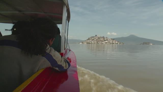 pov boat in lake patzcuaro moving towards janitzio island / patzcuaro, michoacan, mexico - michoacán video stock e b–roll