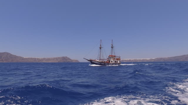 boat in the santorini caldera with view to calderaside of oia in greece the santorini caldera is one of the natural wonders on planet earth the... - oia santorini stock videos & royalty-free footage