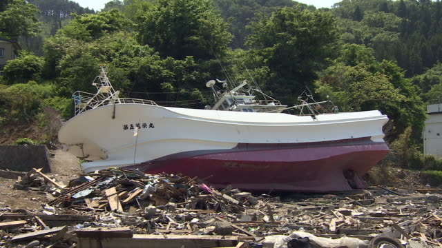 A boat is beached inland after a tsunami.