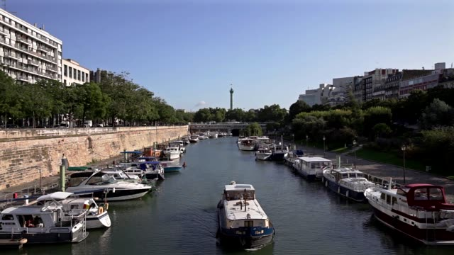vídeos de stock, filmes e b-roll de a boat is cruising between boats of arsenal port where seine river and saintmartin canal link in the background the column of july at place de la... - bastille
