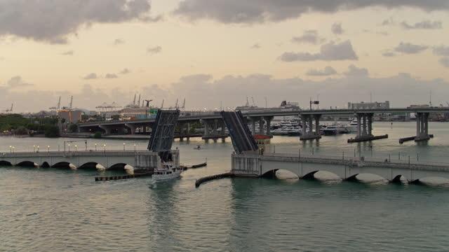 stockvideo's en b-roll-footage met een boot passeert onder de geopende venetiaanse causeway bridge in de vroege ochtend. het centrum van miami, florida. luchtbeelden met de panning-orbiting camera beweging. - venetian causeway bridge