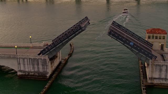 stockvideo's en b-roll-footage met een boot passeert onder de geopende venetiaanse causeway bridge in de vroege ochtend. het centrum van miami, florida. luchtopnamen met de voorwaartse en kantelende filmische complexe camerabeweging. - venetian causeway bridge
