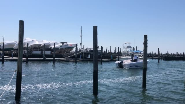 boat leaves the marina at the blue water yacht club. marinas in new york state can open on a limited basis, governor andrew cuomo announced in a... - marina stock videos & royalty-free footage