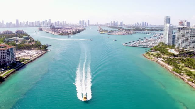 boat leaving port of miami aerial - jachthafen stock-videos und b-roll-filmmaterial