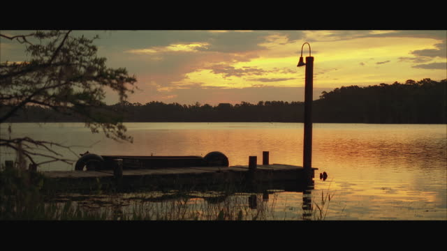 ws boat moored at wooden pier on lake at sunset - moored stock videos & royalty-free footage