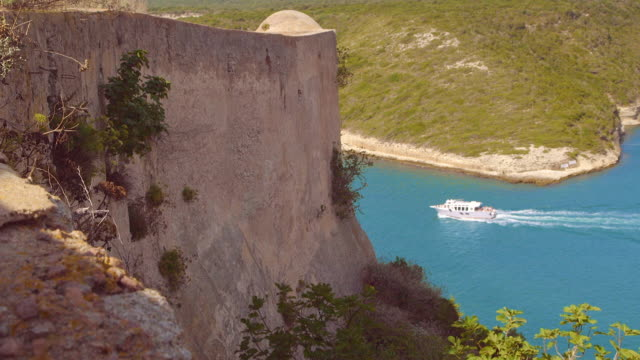 Boat moving by old fortress, Dolly shot in Calvi Corsica, Mediterranean