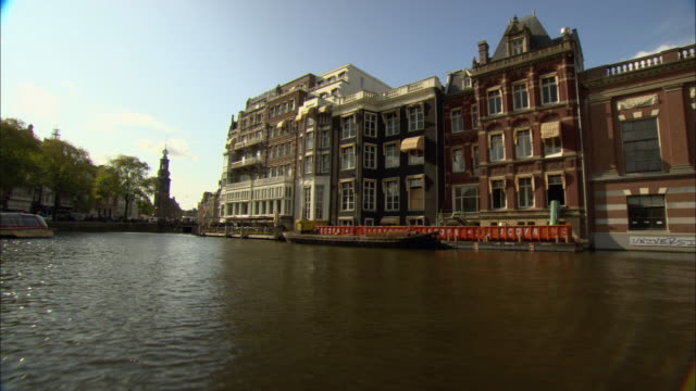 pov boat moving down canal, approaching to old buildings / amsterdam, holland - boat point of view stock videos and b-roll footage