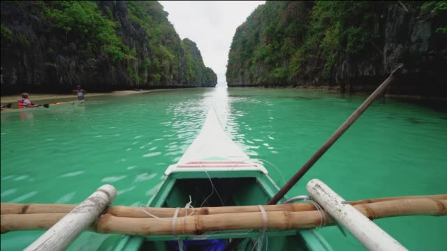 boat moving forward to tropical island with rocks, palawan, philippines - philippines stock videos & royalty-free footage