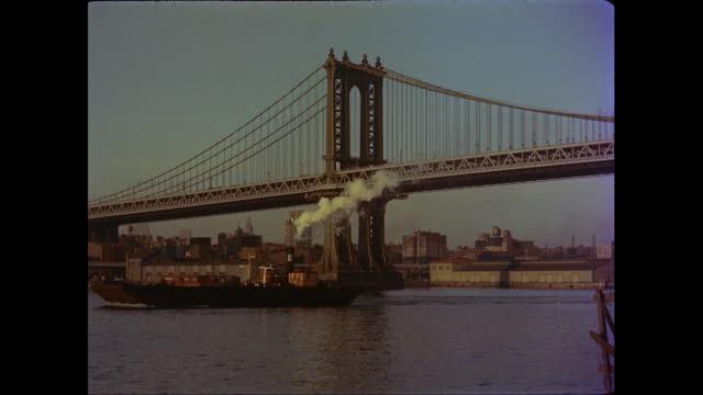 vídeos de stock, filmes e b-roll de ws boat moving in east river with manhattan bridge / new york city, new york state, united states - manhattan bridge