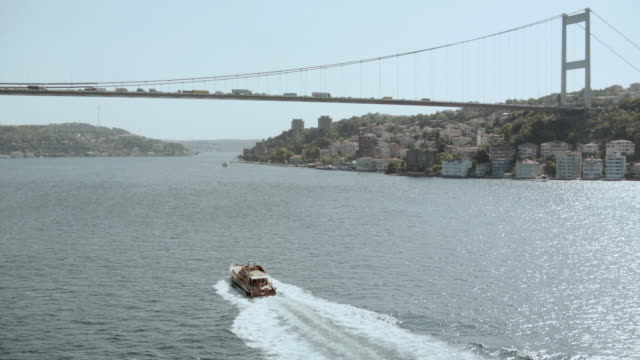 aerial boat moving through the water towards the bosphorus bridge / istanbul, turkey - july 15 martyrs' bridge stock videos & royalty-free footage