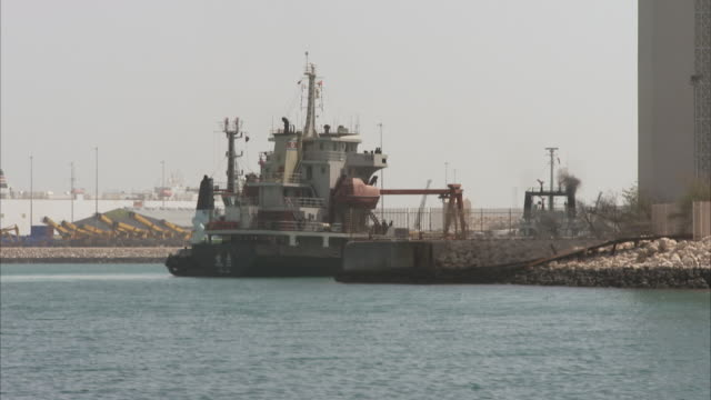 ms pov boat of harbor and tall tug boats moored side on beach / doha, qatar - harbour stock videos & royalty-free footage