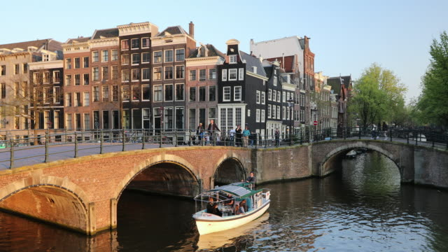 boat on keizersgracht canal, amsterdam, netherlands, europe - arch bridge stock videos and b-roll footage