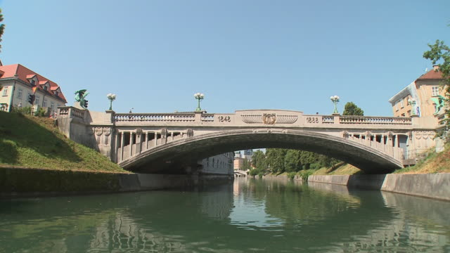 pov boat on ljubljanica river, passing under dragon's bridge (art nouveau style), ljubljana, slovenia - slovenia stock videos & royalty-free footage