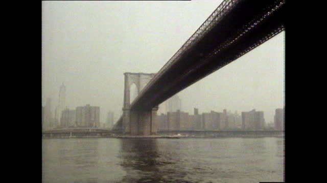 boat pov on river in new york passing under brooklyn bridge; 1980 - suspension bridge stock videos & royalty-free footage