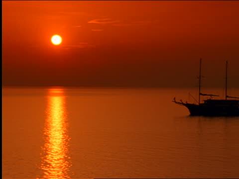 vídeos de stock, filmes e b-roll de silhouette boat on sea at sunset / greece - céu romântico