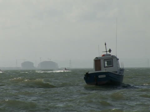 boat on sea, jet ski, industry in distance - acquascooter video stock e b–roll