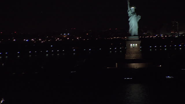 aerial boat on water near the statue of liberty, lit up at night / new york city, new york, united states - 自由の女神点の映像素材/bロール