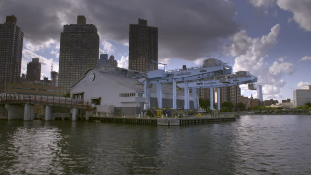 A boat passes a river sanitation building in Manhattan.
