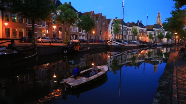 "boat passes on a canal at dusk, the ""aa-kerk"" historic former parish church as background on july 11, 2020 in groningen, netherlands. groningen is a... - former stock videos & royalty-free footage"