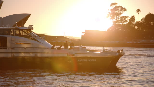 boat passes sydney opera house at sunrise - passenger craft stock videos & royalty-free footage