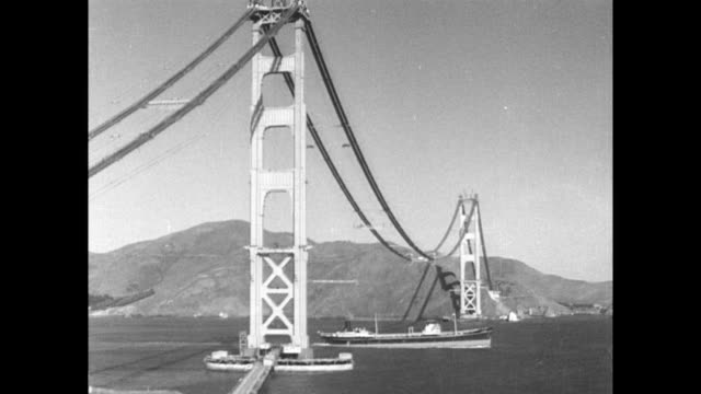 vídeos de stock, filmes e b-roll de / boat passes underneath golden gate bridge / fly wheels running along cables during the construction / workers catch the fly wheel and secure the... - golden gate bridge