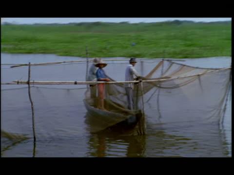 vídeos de stock e filmes b-roll de side pov, boat passing fishermen arranging fishing net on mekong river, china - sampana