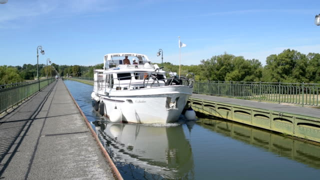 vídeos de stock e filmes b-roll de boat passing over briare pont canal on canal lateral, loire river - enfeites para a cabeça