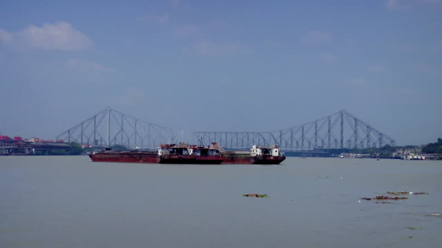 ws boat passing through river near howrah bridge / kolkata, west bengal, india - howrabron bildbanksvideor och videomaterial från bakom kulisserna