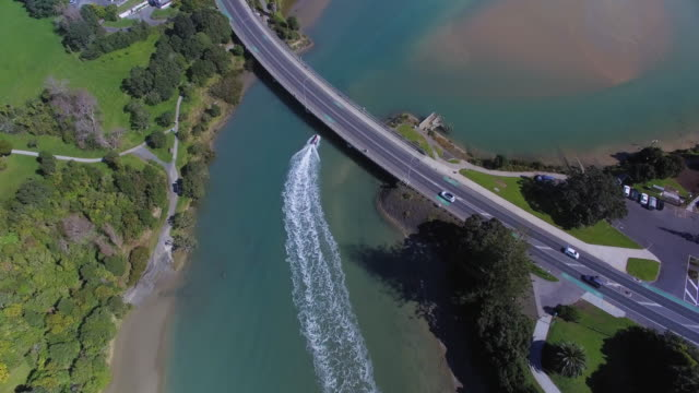 Boat passing underneath bridge in small town of Orewa, Auckland, New Zealand.