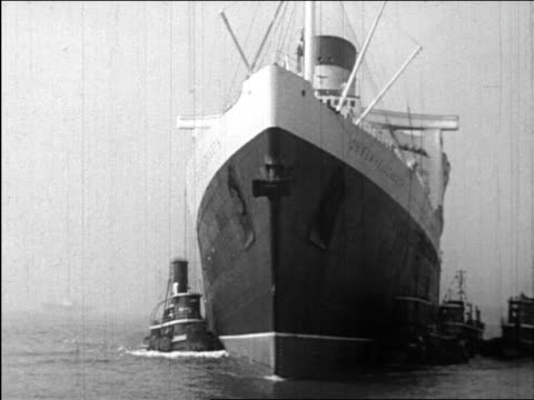 b/w 1947 boat point of view around bow of queen elizabeth liner with many tugboats around it / newsreel - 1947年点の映像素材/bロール