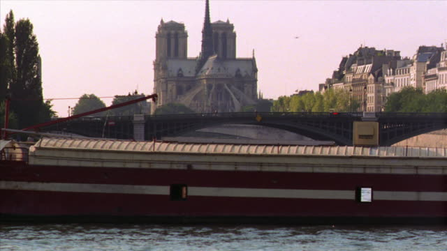 boat point of view barge passing on seine river with notre-dame + pont sully in background / paris, france - barge stock videos & royalty-free footage