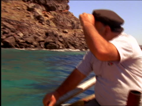 Boat point of view fisherman adjusting cap in small boat / rocky shore in background / Santorini, Greece